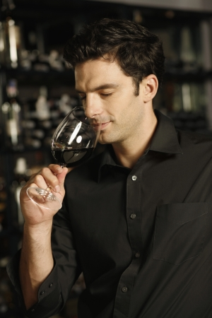 sniffing: Man enjoying a glass of red wine