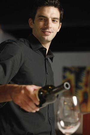 angle bar: Man pouring wine into glass Stock Photo