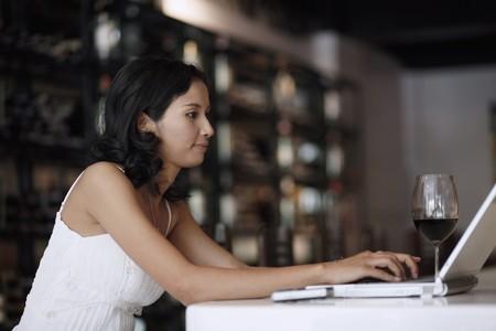Woman using laptop at the bar photo