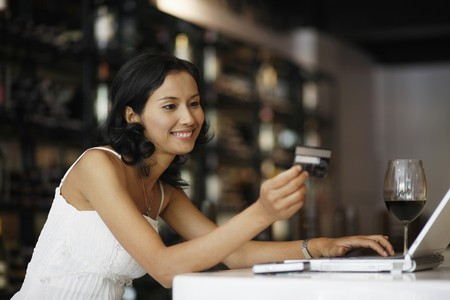 Woman looking at credit card while using laptop Stock Photo - 7360495