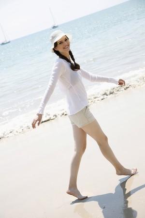 Woman walking along the beach photo
