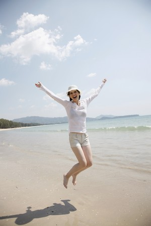 southeastern european descent: Woman jumping on the beach with her arms raised