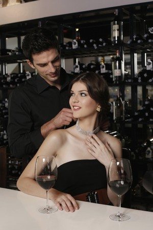 side bar: Man fastening womans necklace