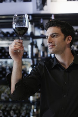 Man inspecting a glass of red wine photo