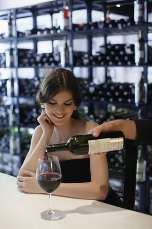 Woman waiting for her wine to be poured Stock Photo - 7360519