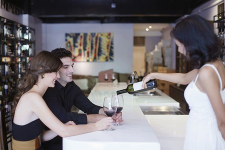 southeastern european descent: Waitress pouring wine for man and woman at the bar Stock Photo