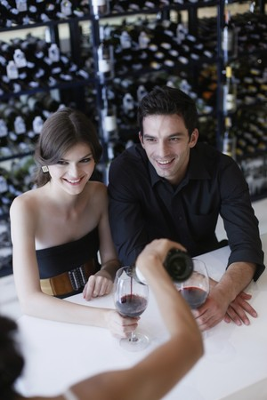 Man and woman waiting for their wine to be poured photo