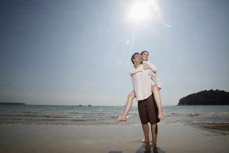 Man giving woman a piggy back ride on beach photo