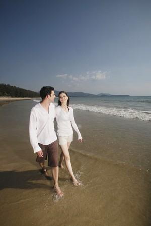 Man and woman walking along the beach Stock Photo - 7360963