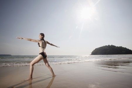 Woman practising yoga on beach photo