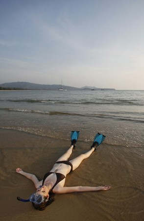 Woman with snorkeling gear lying on the beach photo