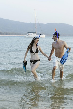 Man and woman running through water, holding flippers Stock Photo - 7360996