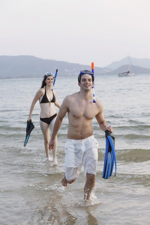 Man and woman running through water, holding flippers photo