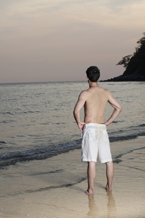 Man standing with arms akimbo on the beach photo