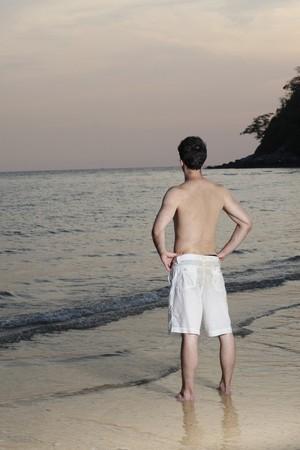 mani sui fianchi: Uomo in piedi con le braccia akimbo sulla spiaggia  Archivio Fotografico