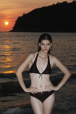 Woman standing with arms akimbo on the beach photo