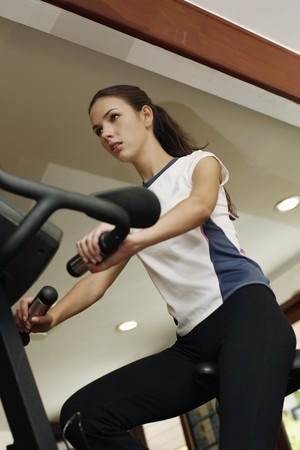Woman on exercise bike at gym photo