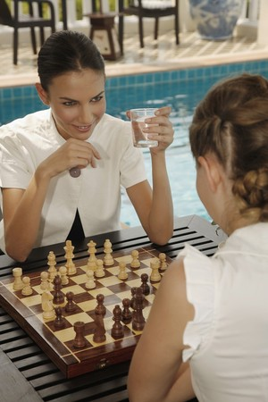 Businesswomen playing chess by the poolside Stock Photo - 7360801
