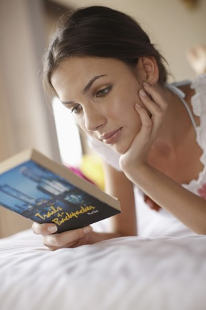 Woman reading book on bed photo