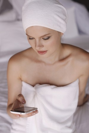 towel wrapped: Woman with towel wrapped around head text messaging on phone