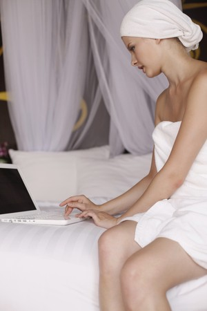 Woman with towel wrapped around head using laptop photo