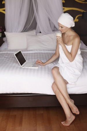 legs crossed at knee: Woman wrapped in towel using laptop and holding a cup of coffee