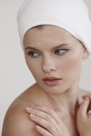 Woman with towel wrapped around head, hands crossed over chest photo