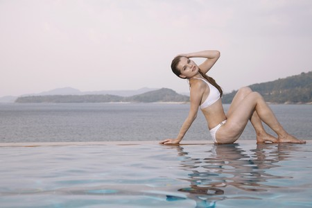 Woman sitting at the edge of pool photo