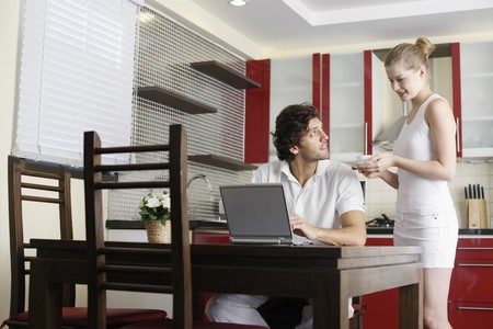 Woman serving man a cup of coffee, man using laptop Stock Photo - 7360845