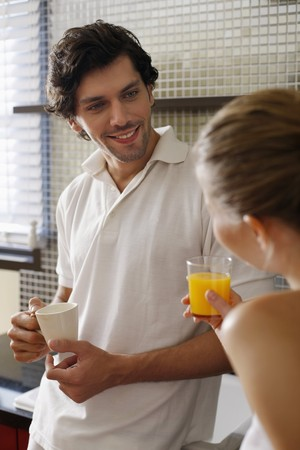 Couple enjoying beverages in the kitchen photo