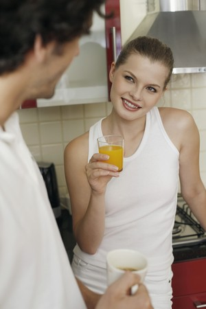 Couple enjoying beverages in the kitchen Stock Photo - 7359250