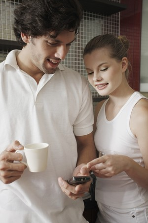 Couple looking at text message while enjoying beverages photo