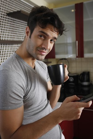 Man enjoying a cup of coffee while text messaging photo