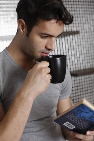 hombre tomando cafe: Hombre que goza de una taza de café al leer el libro