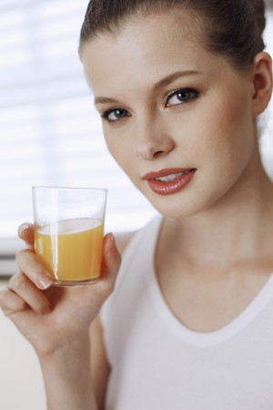 Woman holding a glass of orange juice photo