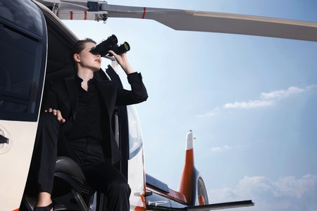 Businesswoman looking through binoculars from helicopter photo