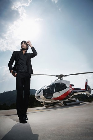 helipad: Businessman standing at helipad with helicopter in the background