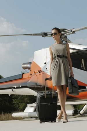 Businesswoman with luggage and briefcase walking away from helicopter Stock Photo - 7359198