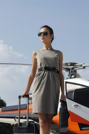 Businesswoman with luggage and briefcase standing by the helicopter photo