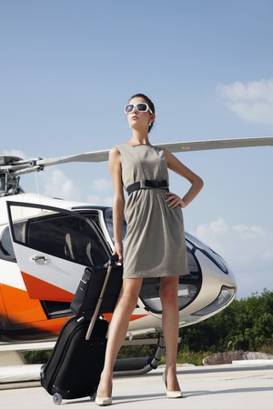 bagage: Businesswoman with luggage and briefcase standing by helicopter