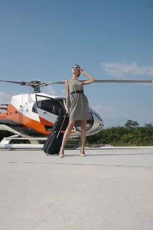 Businesswoman with luggage and briefcase standing by helicopter photo
