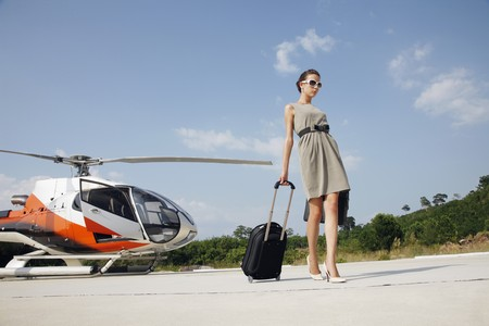 ukrainian ethnicity: Businesswoman with luggage and briefcase walking away from helicopter Stock Photo