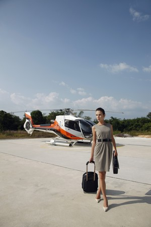 Businesswoman with luggage and briefcase walking away from helicopter Stock Photo - 7360878