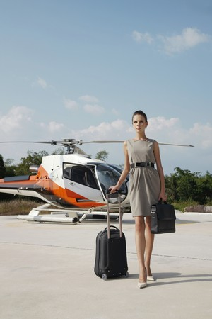 Businesswoman with luggage and briefcase walking away from helicopter photo