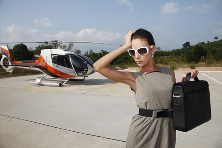 Businesswoman holding briefcase with helicopter in the background photo