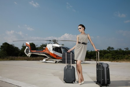 helipad: Businesswoman with luggages and briefcase standing at helipad, helicopter in the background Stock Photo