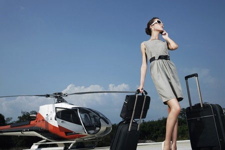Businesswoman with luggages and briefcase talking on the phone at helipad Stock Photo - 7360633