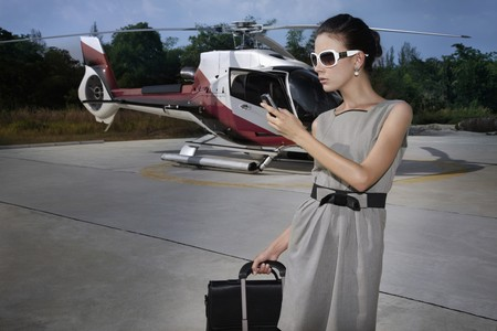 helipad: Businesswoman with luggages and briefcase text messaging on phone at helipad Stock Photo