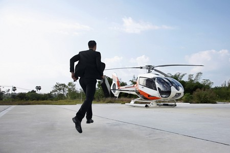 Businessman running towards helicopter photo