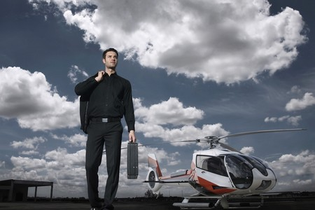 Businessman with briefcase standing at helipad, helicopter in the background Stock Photo - 7360533